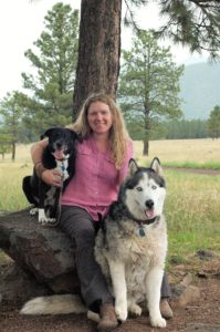 Dr. Dobbin sitting under a pine tree with her two dogs