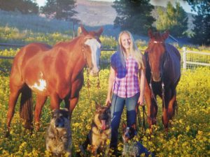 Dr Bruchman posing with her 2 horse, and 3 dogs in a field of flowers