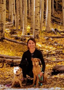 Lauren with her 2 dogs, posing in the forest with white barked aspen trees.